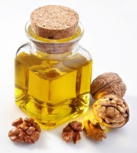 Walnut oil with nuts on a white background