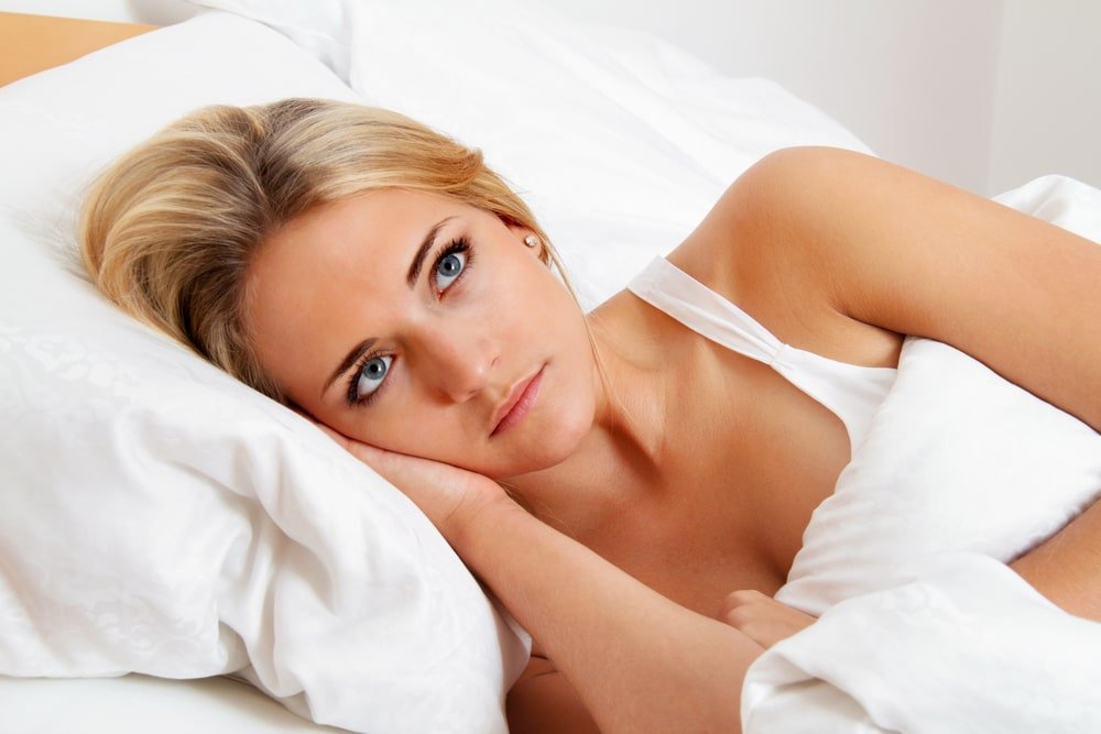 Women lying in bed sleepless, local and online hypnosis for sleep