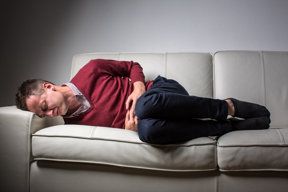 man laying on the sofa, holding his tummy, local and online hypnosis for crohn's disease