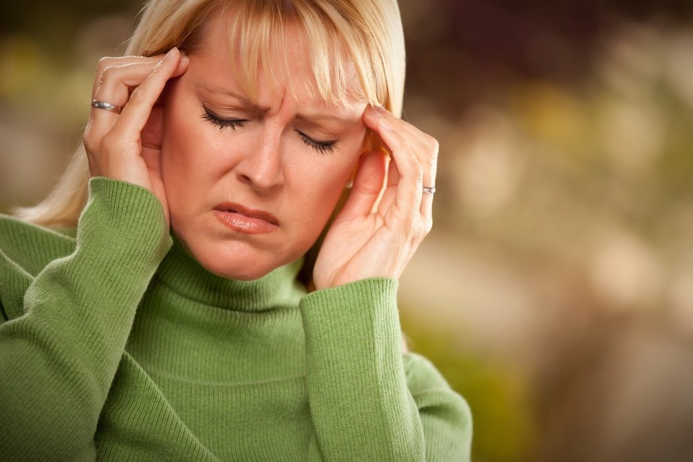woman holding her head, fighting with chronic migraines. Integrative Hypnotherapy in Boca Raton FL offer local and online hypnosis for migraines