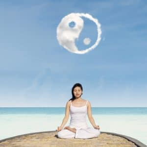 asian woman in lotus seat, meditating under a yin and yang symbol in the sky, balancing masculine and feminine energy