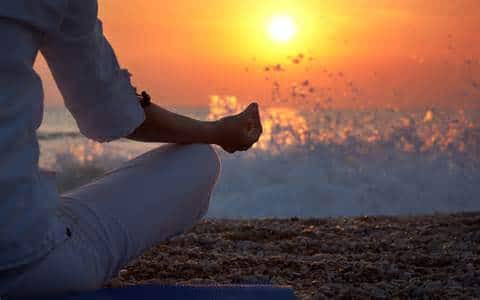 a woman meditating on the beach, symbolizing the power of mindfulness