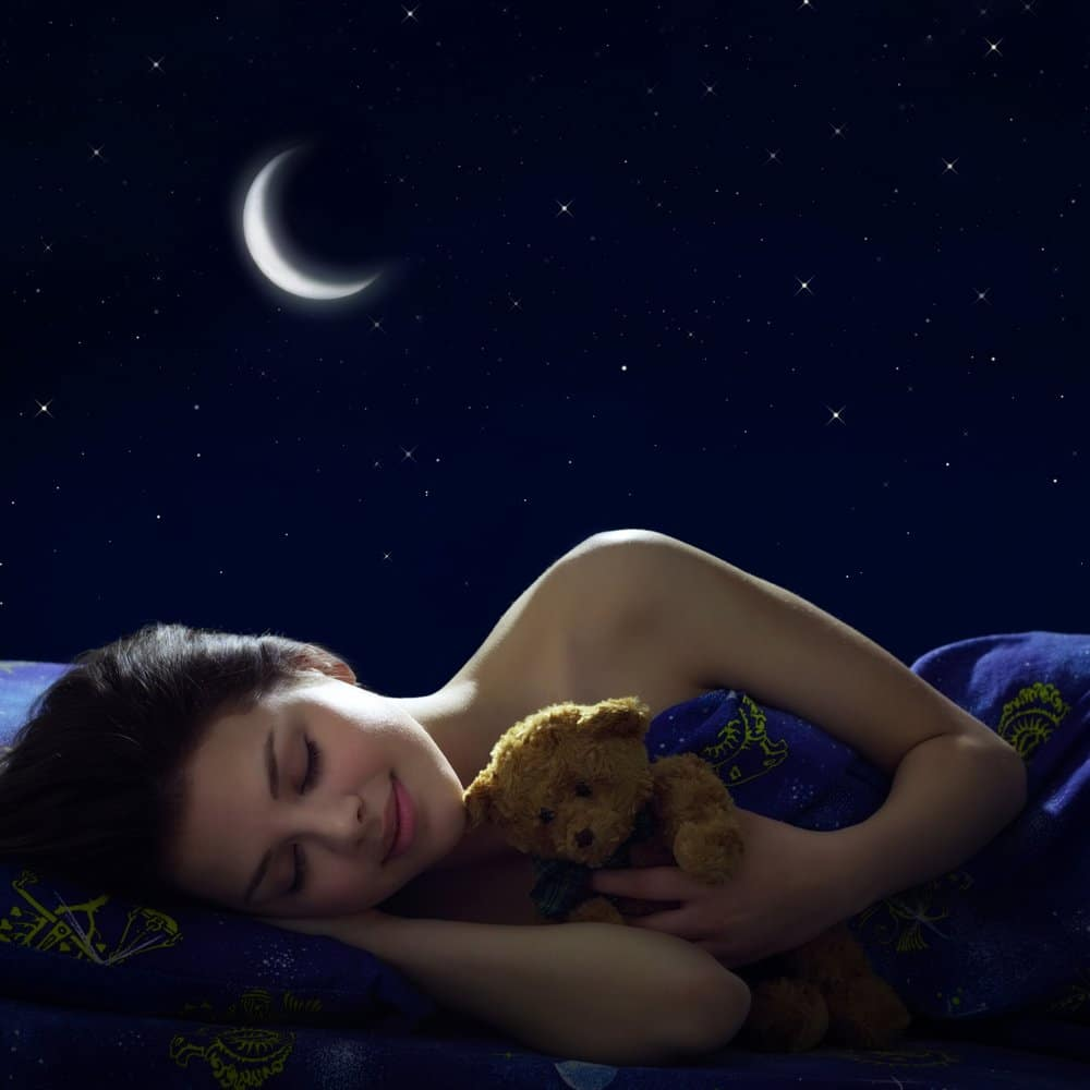 woman with black hair and teddy bear, laying in her bed and sleeping