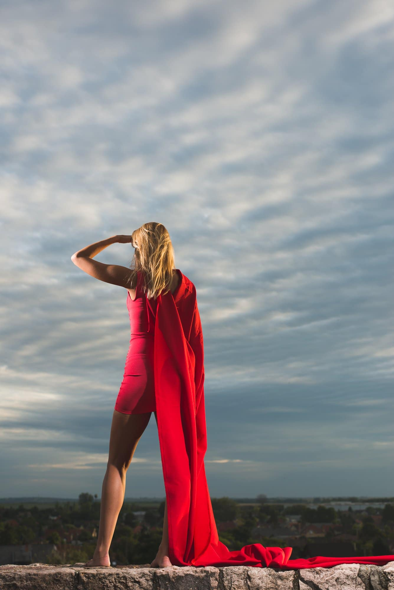 woman with long blonde hair and red long cape dress on top of hill, overseeing the valley, Steps to Take During the Coronavirus Pandemic
