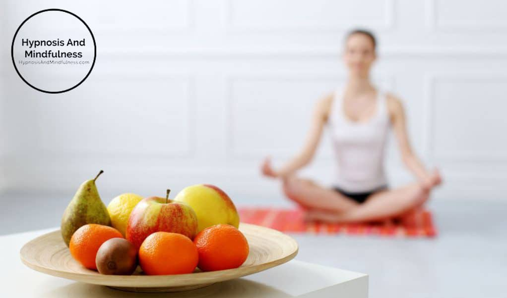 woman in yoga pose on yoga mat, wooden bowl with fresh fruit in the front on little table, mindful eating