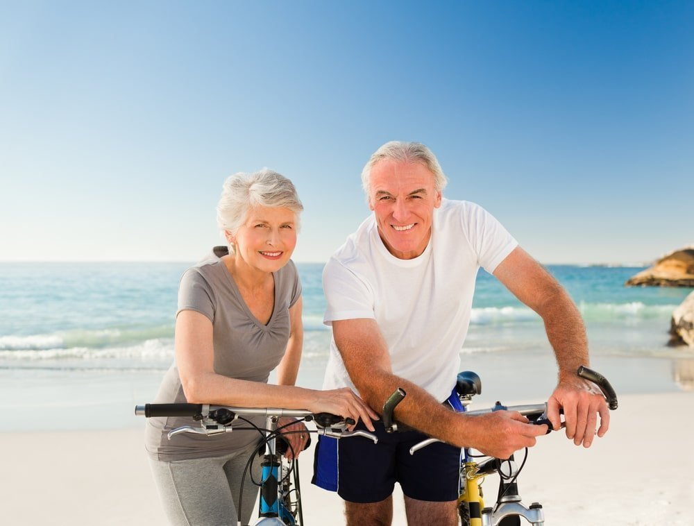 a woman and man with white hair and fitness outfit, bicycles in front of them, on the beach, whould you prefer to age gracefuly with mindfulness?