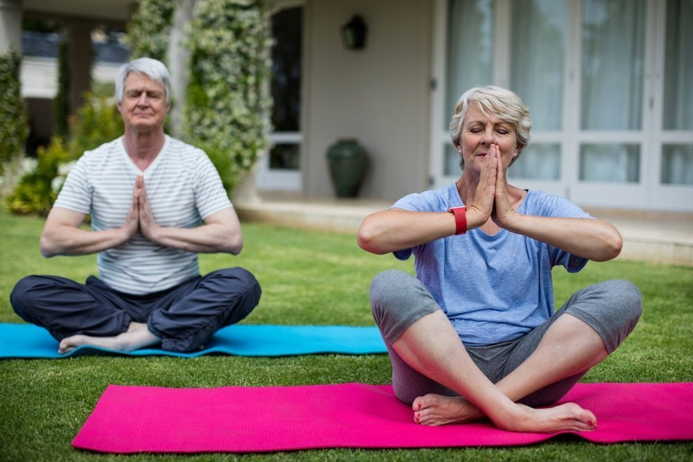 a woman and man with white hair sitting on their yoga mats, aging and mindfulness ensure GREATER WELL-BEING