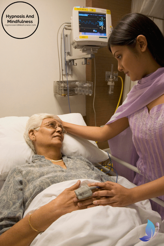 a young Indian woman holding the hand of an elder woman in the hospital, moving from empathy to compassion