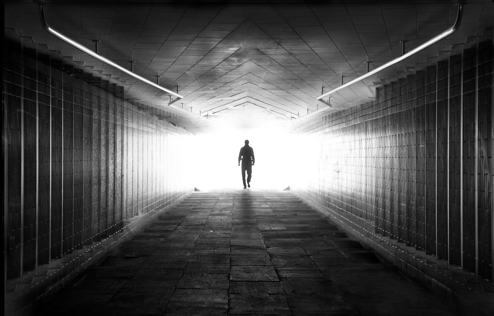 a person walking through a dark tunnel, end of life care
