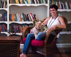 Shirly Gilad in her library with her dog Leslie
